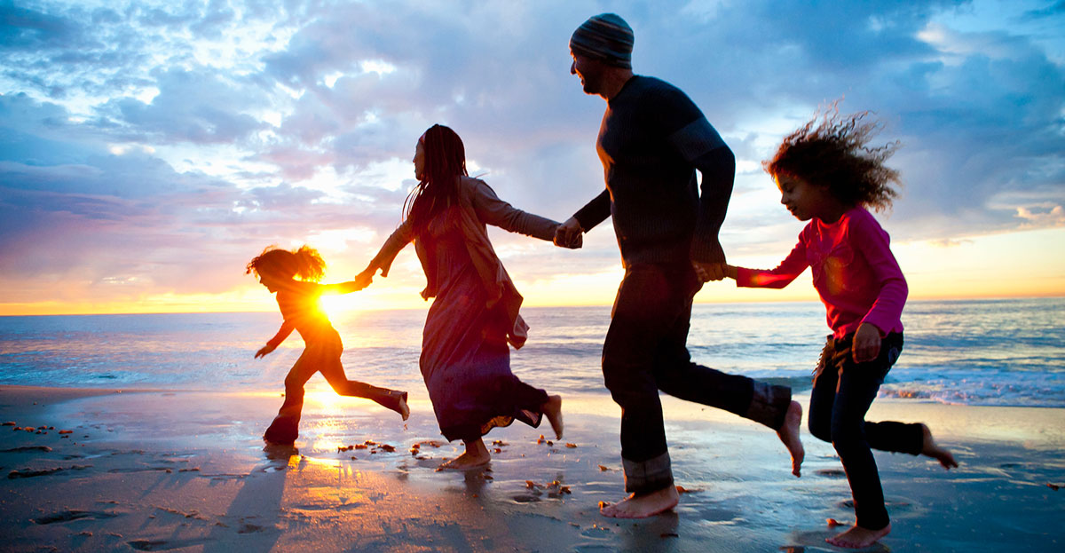 Family of four running from waves while the sun rises.